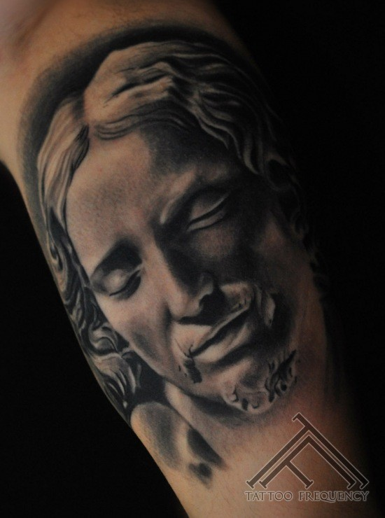 Gray washed style medium size biceps tattoo of antic statue