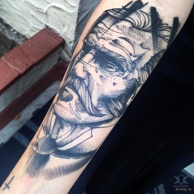 Gray washed style mystical looking forearm tattoo of man portrait