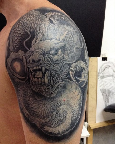 Gray washed style realistic looking shoulder tattoo of fantasy dragon