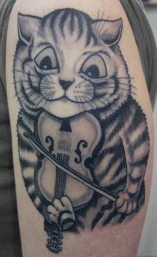 Gray washed style small funny looking cat with violin tattoo on shoulder