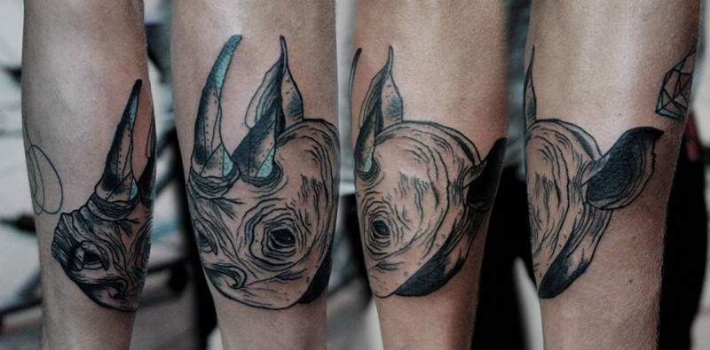 Gray washed style small rhino head tattoo on leg