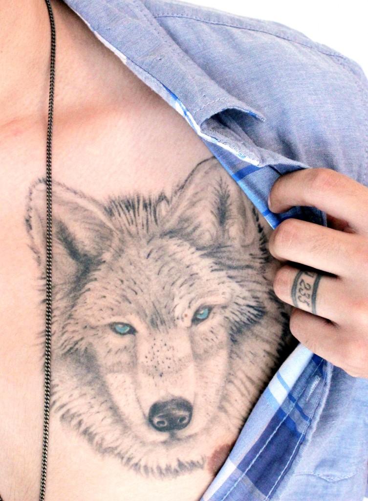 lupo grigio con occhi blu tatuaggio sul petto