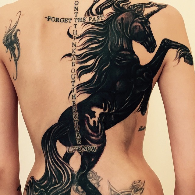 Great dark horse and quotes tattoo on whole back