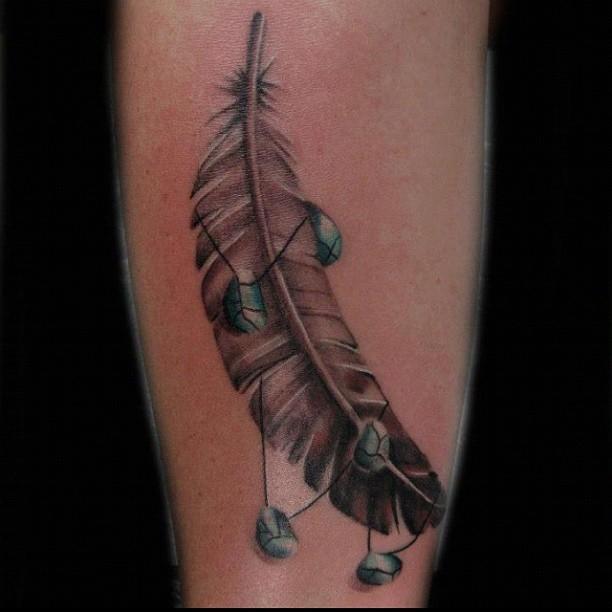particolare inchiostro grigio piuma di aquila con piccole rocce tatuaggio