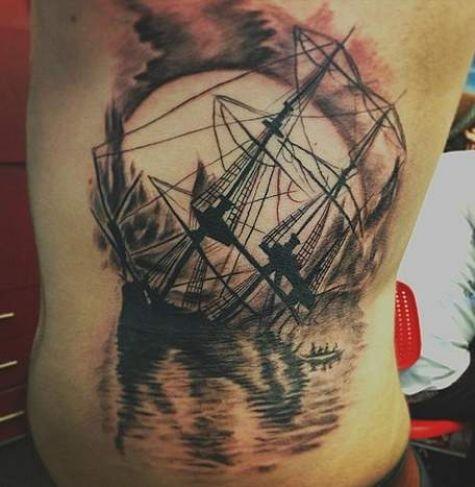 Tatuaggio colorato sulla schiena naufragio della nave a vela & il tramonto