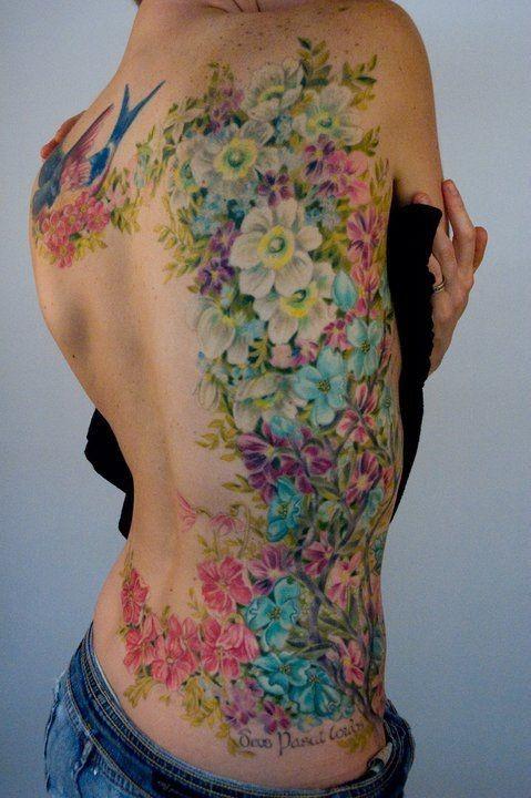 Great wonderful coloured flowers tattoo on ribs