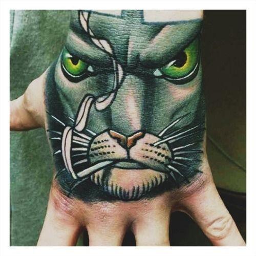 Green cat smoking a cigarette tattoo on hand