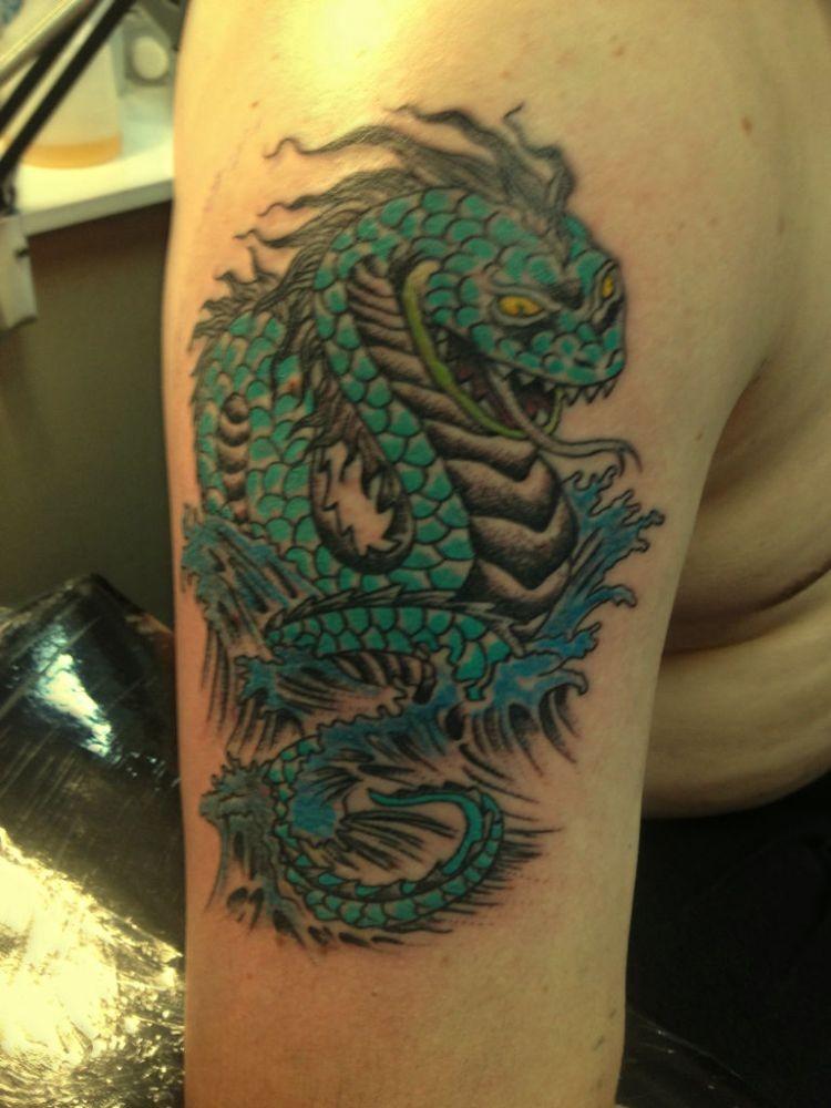 serpente verde tatuaggio sul braccio