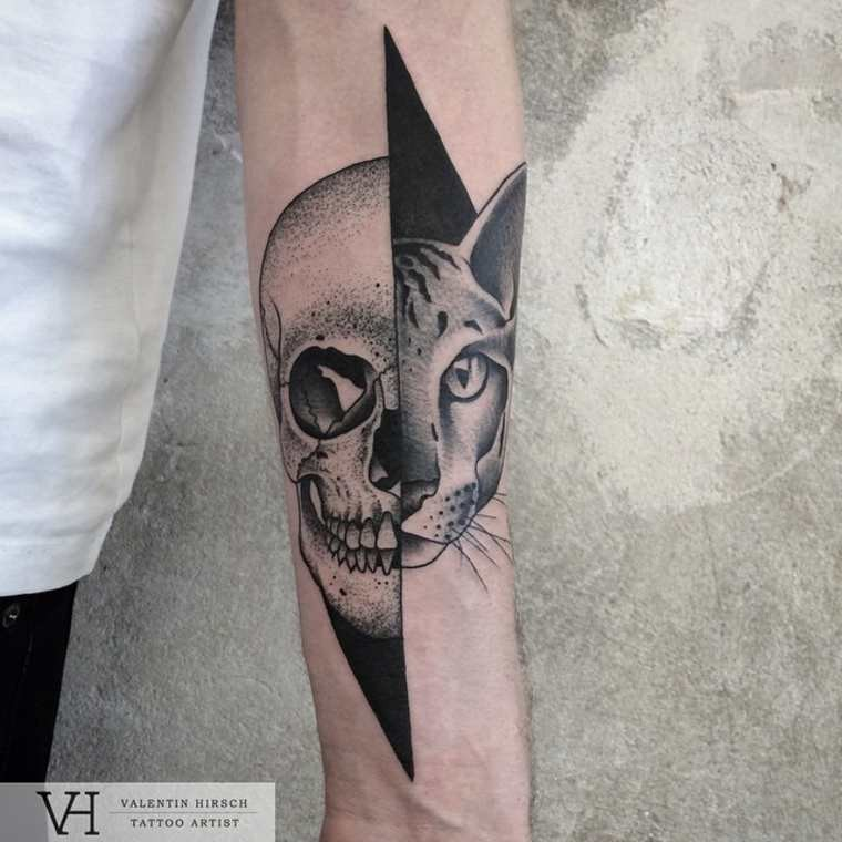 Half geometrical half dot style forearm tattoo of split human skull with cat by Valentin Hirsch