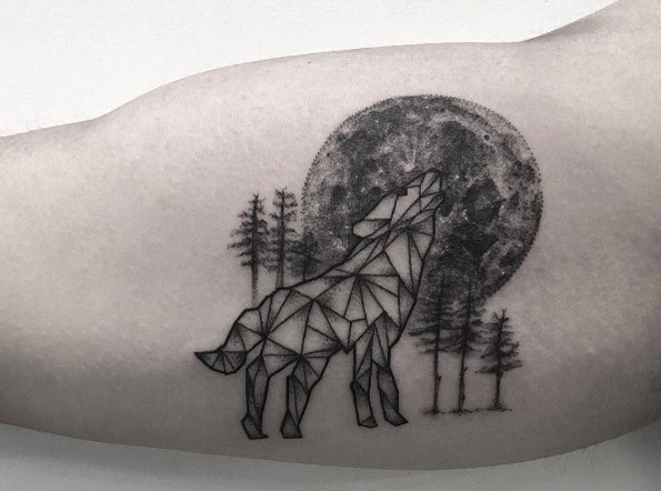 Half realistic half geometrical style biceps tattoo of wolf with large moon and trees