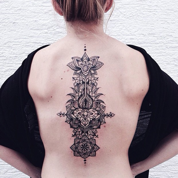 Hinduism style black ink back tattoo of various ornamental flowers