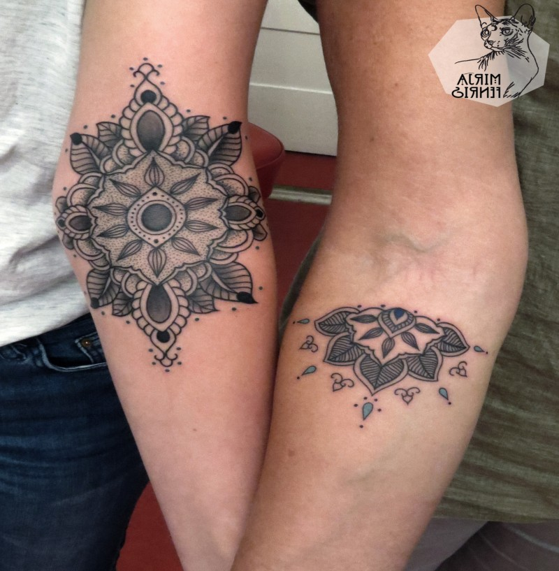 Hinduism style black ink forearm tattoo of small flowers