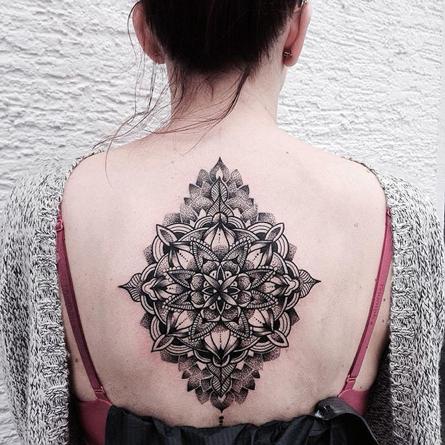 Hinduism style black ink whole back tattoo of beautiful flower
