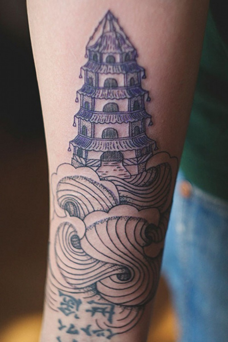 Homemade blue colored temple tattoo on forearm with waves and letteing