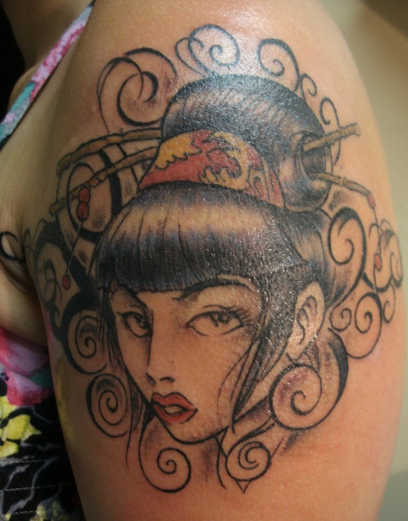Homemade colored small Asian woman portrait tattoo on shoulder