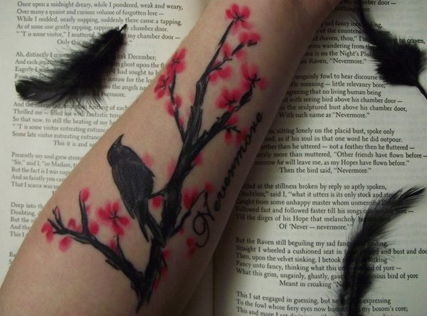 Homemade like black ink crow with blooming tree tattoo on forearm stylized with lettering