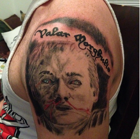 Homemade like colored Game of Thrones hero portrait tattoo on shoulder with lettering