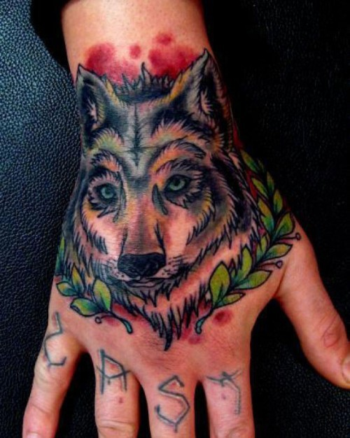 Homemade like colored little wolf tattoo on hand