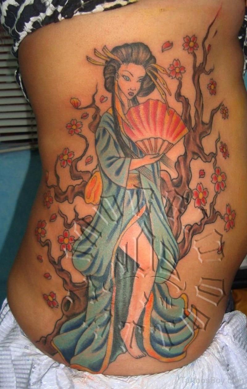 Homemade like painted colored seductive geisha tattoo on side with blooming tree