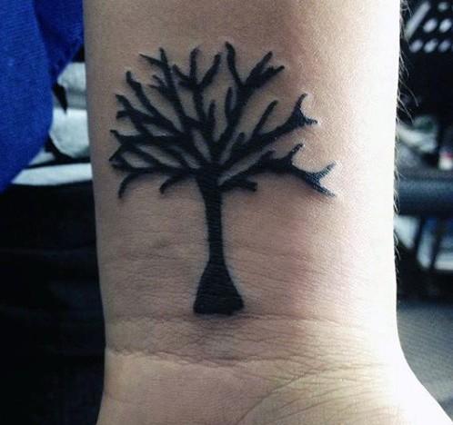 Homemade like tiny black ink tree tattoo on wrist