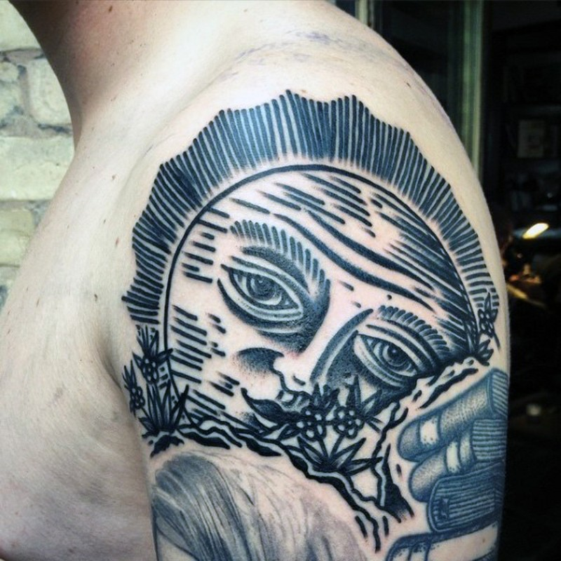 Homemade style black and white big sun tattoo on upper arm