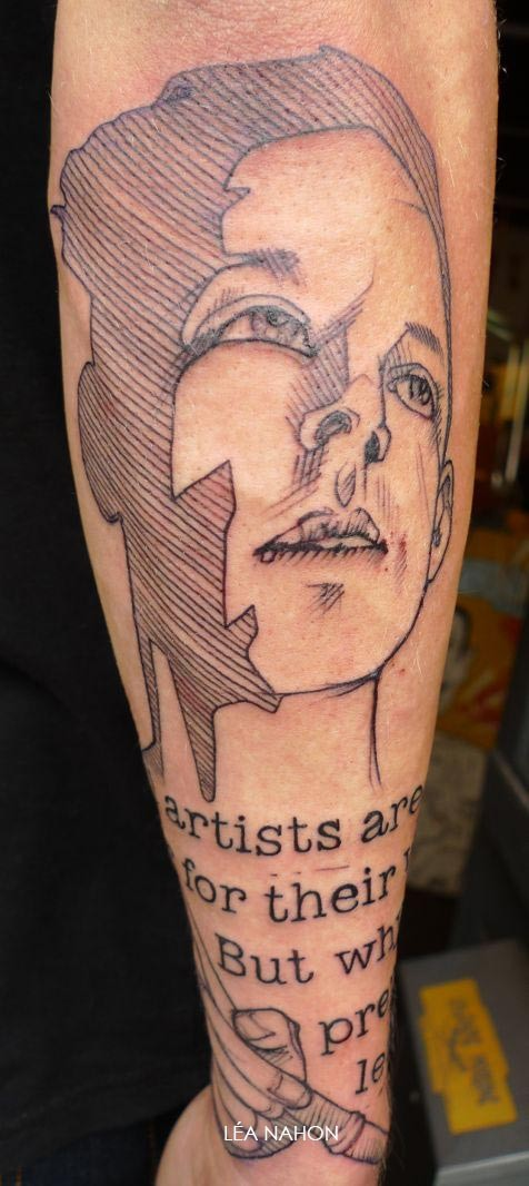 Homemade style black ink arm tattoo of human face with lettering