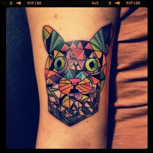 Homemade style colored arm tattoo of cat head with various figures
