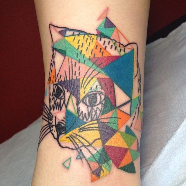 Homemade style colored arm tattoo of cat stylized with geometrical figures