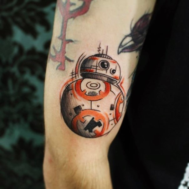 Homemade style colored little new Star Wars droid tattoo on arm area