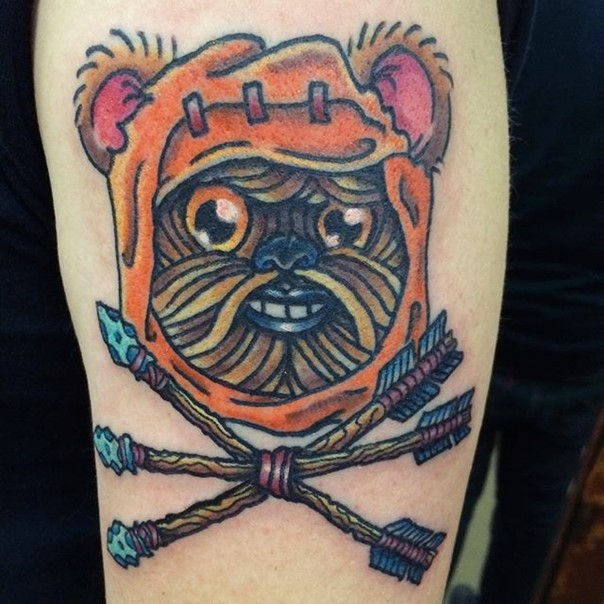 Homemade style colored smiling ewok face tattoo on shoulder with crossed arrows