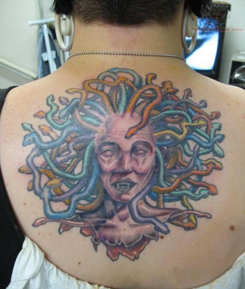 Homemade style colored upper back tattoo of severed Medusa`s head