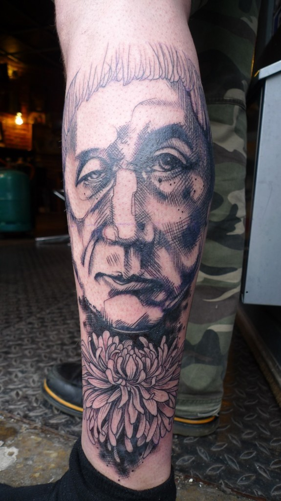 Homemade style detailed leg tattoo of old man portrait