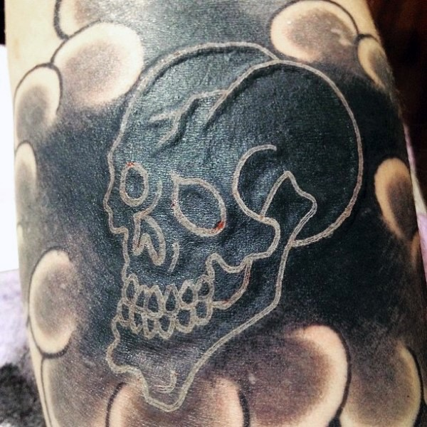 Homemade style little white ink skull tattoo
