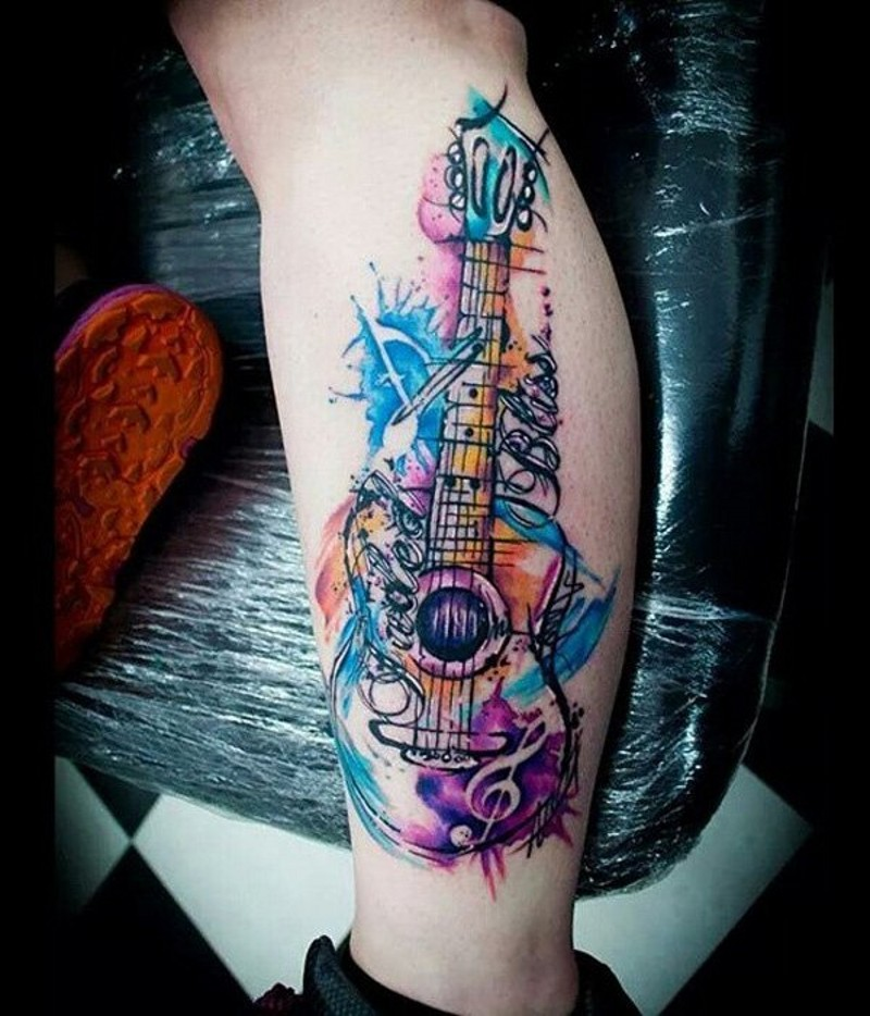 Homemade style multicolored guitar with lettering tattoo on leg