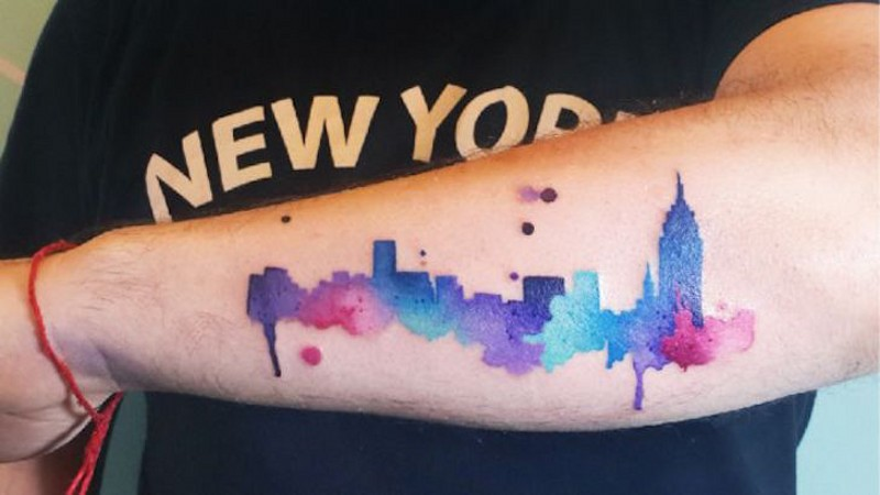 Homemade watercolor style colored forearm tattoo of big city sights