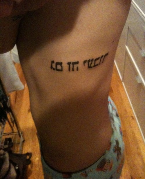 Horizontal hebrew tattoo on ribs