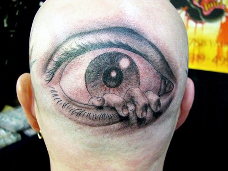 Horrifying like painted black and white eye with hand tattoo on head