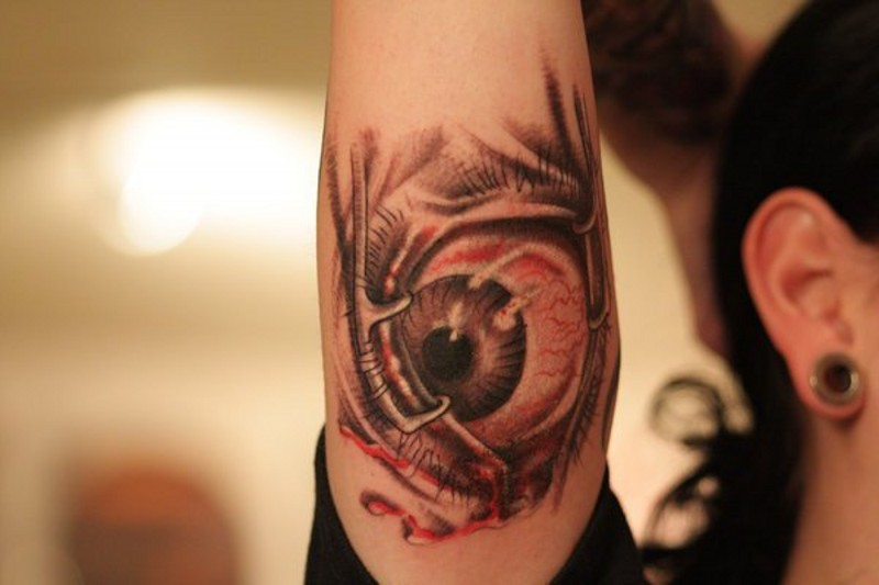 Horrifying painted big colored evil eye tattoo on arm
