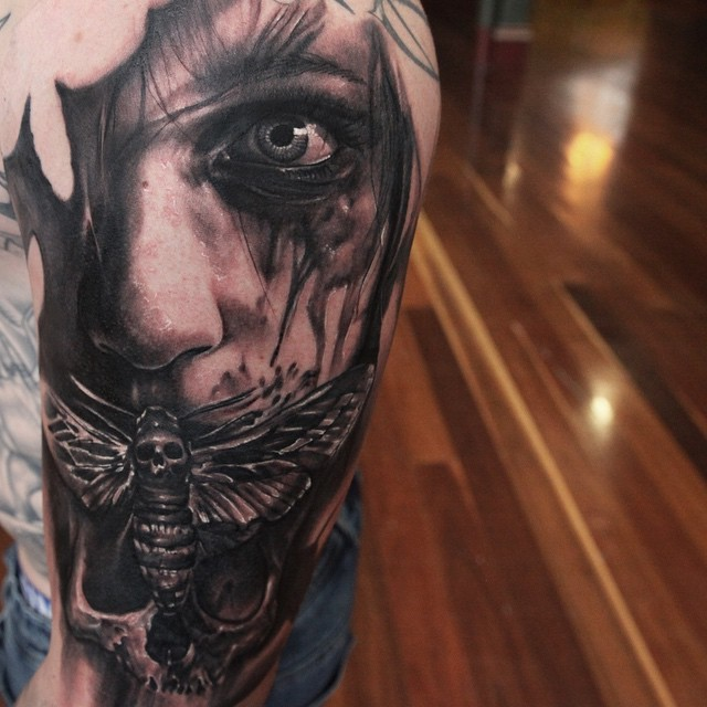 Horrifying painted black and white mystic man with insect and skull tattoo on shoulder