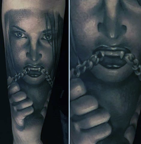 Horrifying painted black and white vampire woman with chain tattoo on sleeve