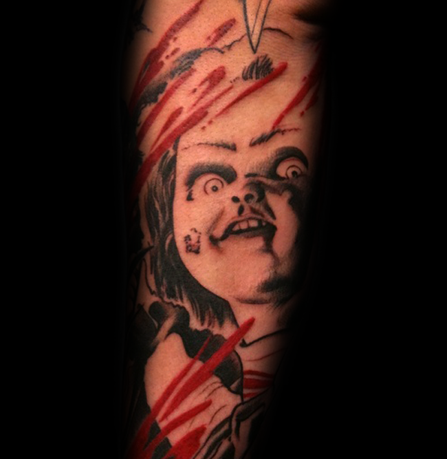 Horror movie doll tattoo on forearm with bloody stripes
