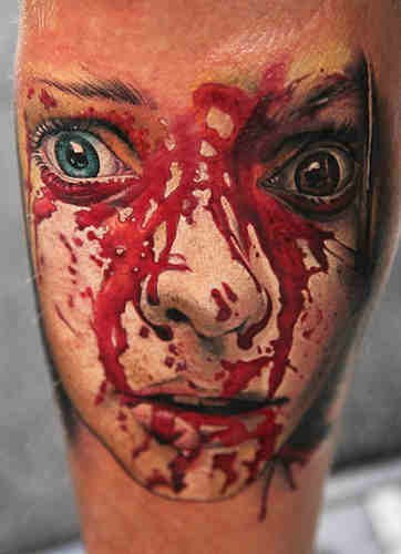 Horror movie like big bloody monster girl face tattoo on leg