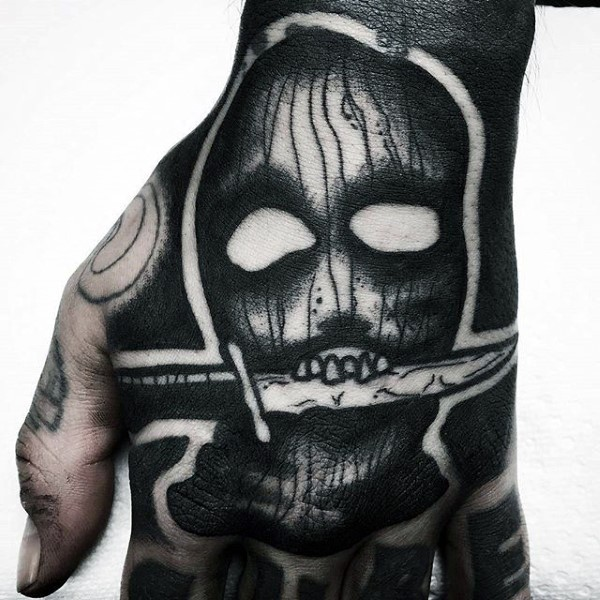 Horror movie like black ink crazy mask with knife tattoo on hand