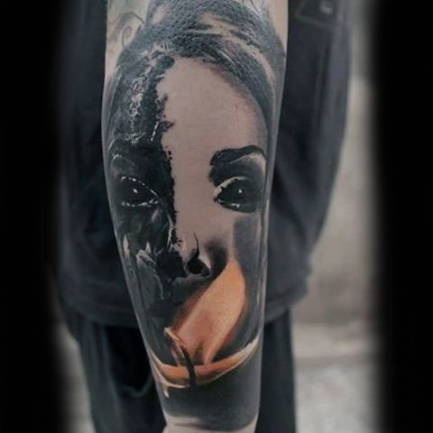 Horror movie like black ink demonic woman face tattoo of forearm combined with flames