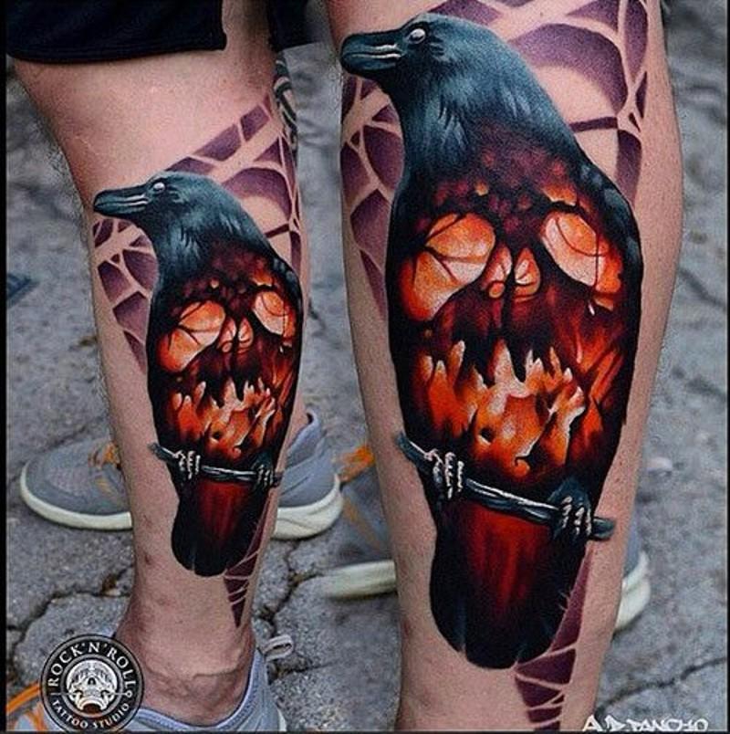 Horror movie like colored big crow stylized with burning skull tattoo on leg