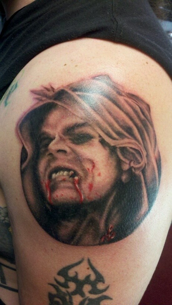 Horror movie like colored bloody vampire tattoo on shoulder