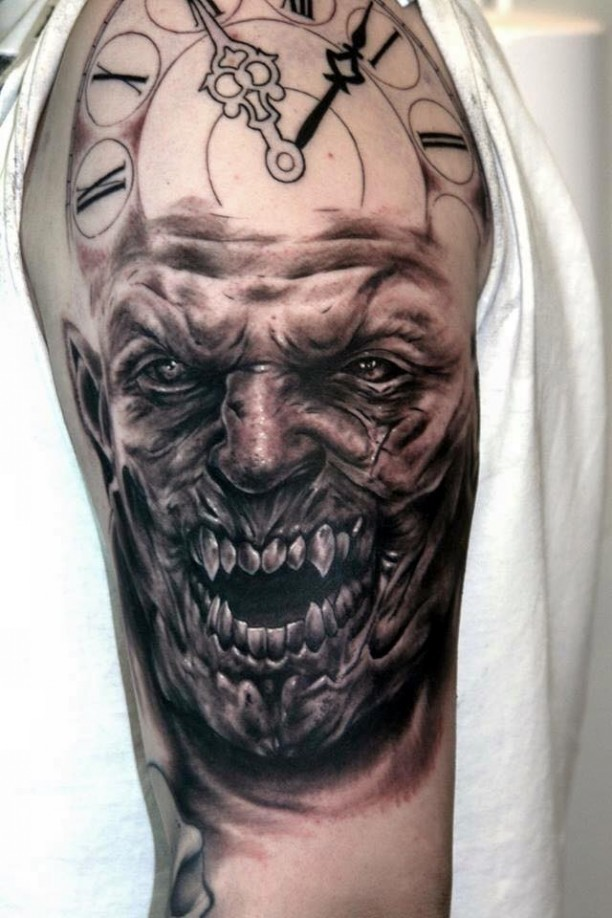 Horror movie like colored detailed monster face tattoo on shoulder with clock