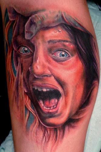 Horror movie like colored scared woman tattoo on leg