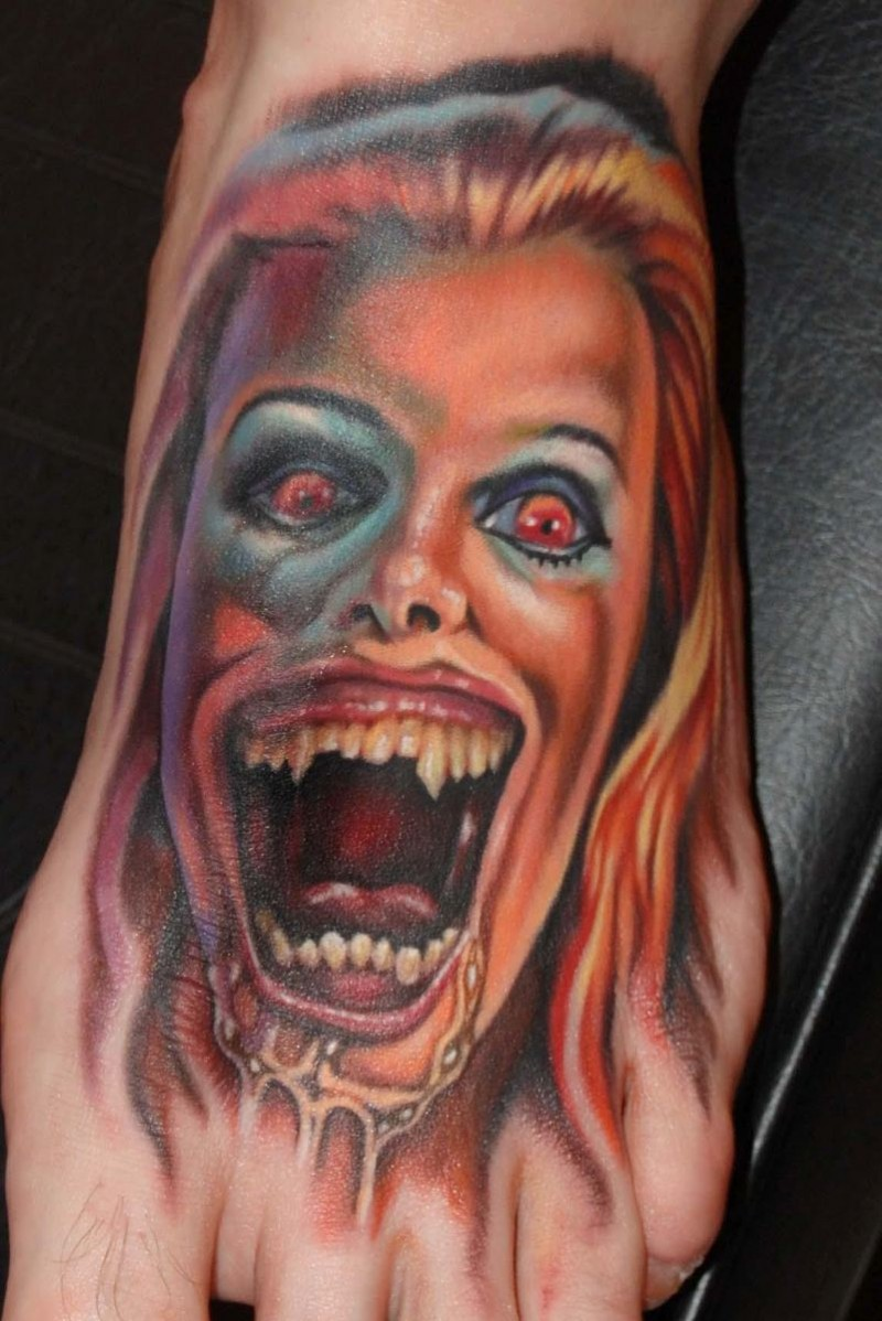 Horror movie like creepy colored female zombie tattoo on foot