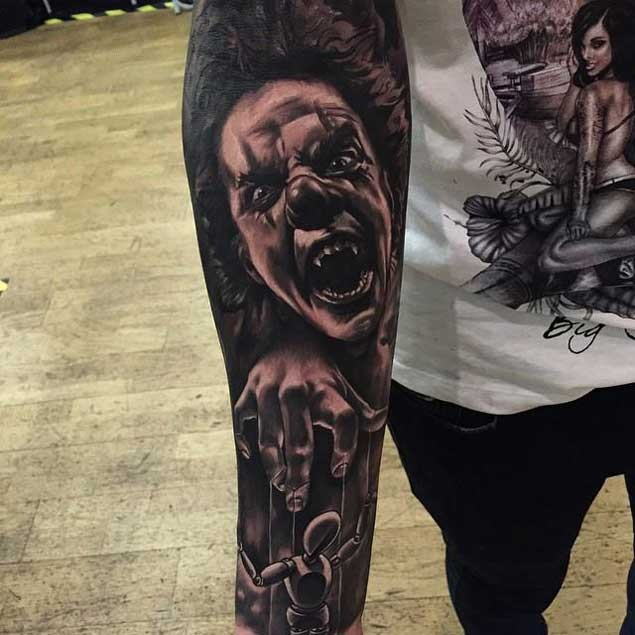 Horror movie style colored evil clown tattoo on sleeve with puppet